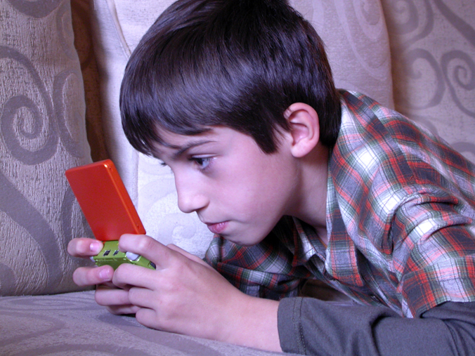 Photo of a young boy playing a handheld video game