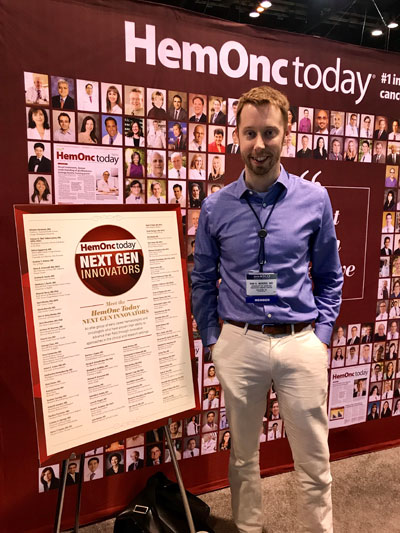 Van Morris, MD, MS, poses in front of a sign with the names of all HemOnc Today Next Gen Innovators. The sign was displayed at HemOnc Today's booth in the exhibit hall at ASCO Annual Meeting.