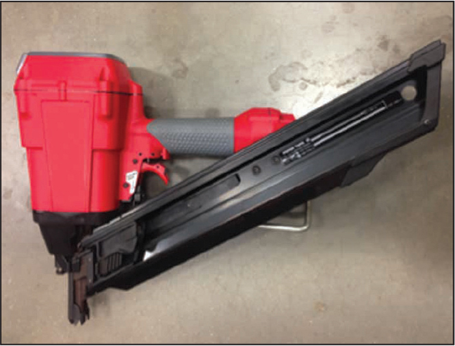 Photograph of commercially available pneumatic nail gun (compressed air hose not shown).