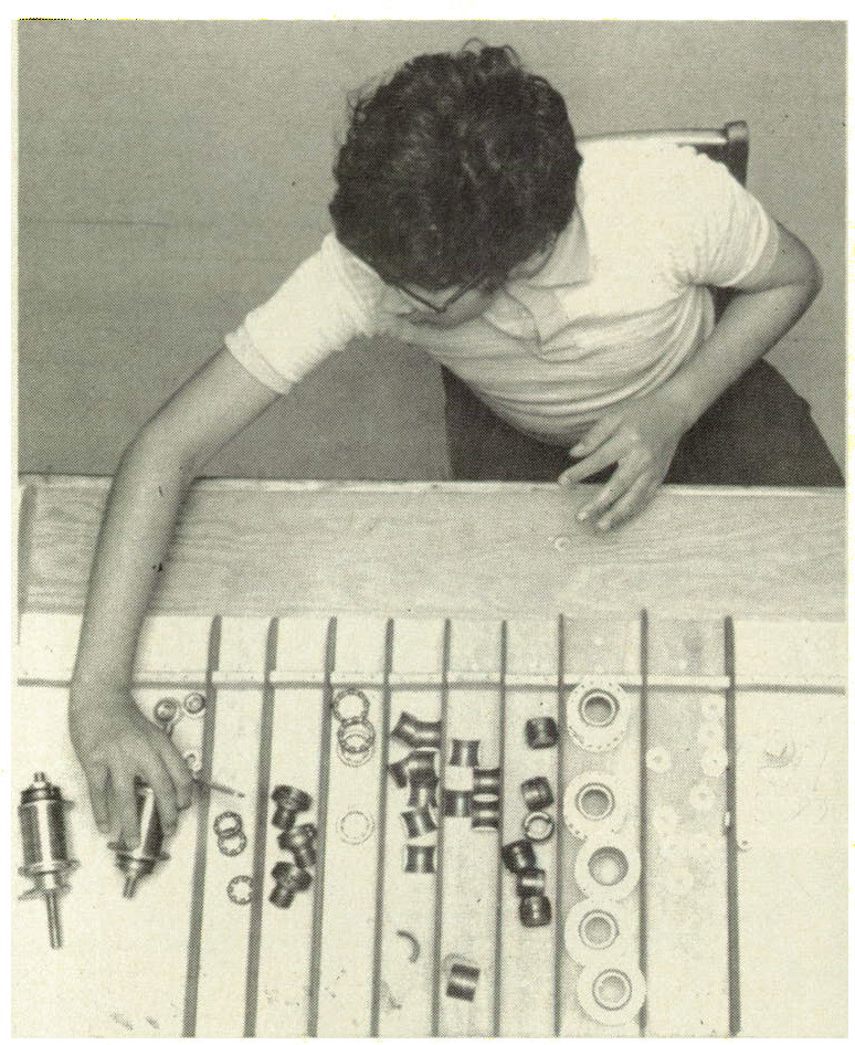 Figure 1. This boy was born deaf and blind as a result of congenital rubella. At a prevocationat workshop at the New York Institute for the Education of the Blind, he is learning how to punch a time clock (left), stock parts (center), and assemble machine components (right).