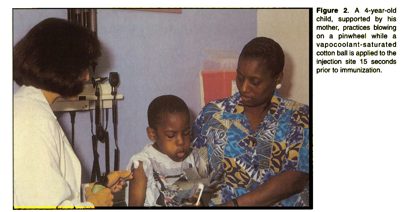 Figure 2. A 4-year-old child, supported by his mother, practices blowing on a pinwheel while a vapocoolant-saturated cotton ball is applied to the injection site 15 seconds prior to immunization.