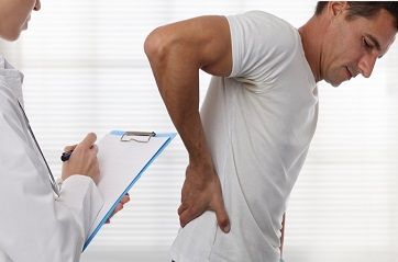 doctor examining patient with back pain