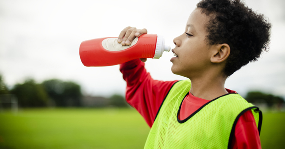Child athlete drinking from bottle